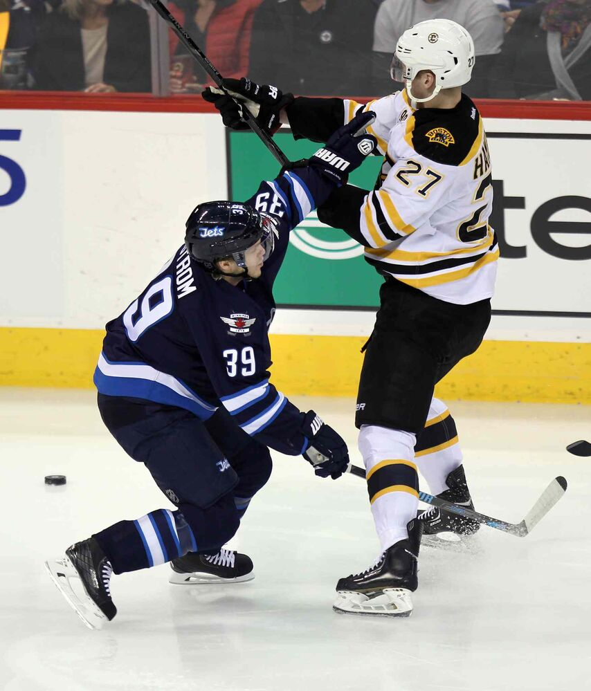 Jets' Tobias Enstrom ties up the Bruins' Dougie Hamilton during the first period of Thursday's game. (Phil Hossack / Winnipeg Free Press)