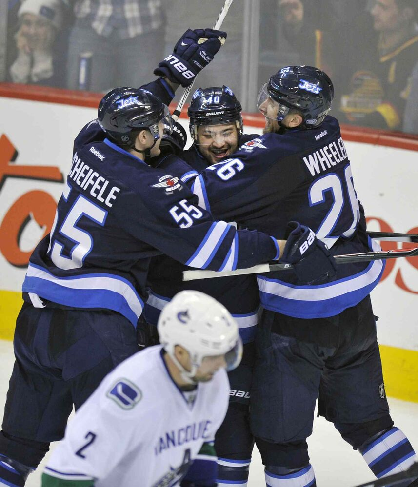 Winnipeg Jets' Devin Setoguchi is congratulated by teammates Mark Scheifele, left, and Blake Wheeler after scoring the game-winning goal against the Vancouver Canucks in Winnipeg Friday night. The Jets beat the Canucks 4-3. (Fred Greenslade / Special to the WINNIPEG FREE PRESS)