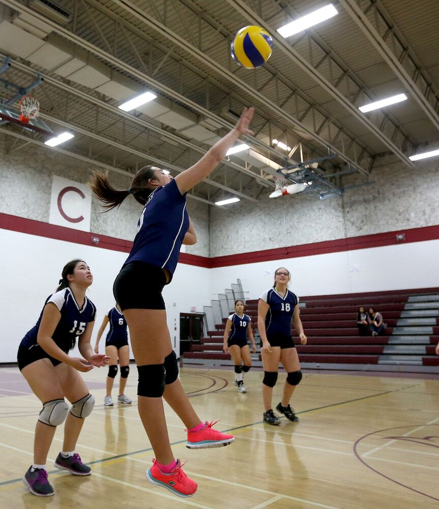 Grant Park Pirates' Courtney Catton hits the ball towards the DMCI Maroons as her teammates look on. (TREVOR HAGAN / WINNIPEG FREE PRESS)
