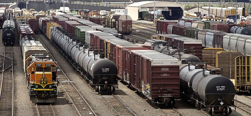Black tank cars used to transport crude oil are parked among other rail traffic at a train yard.