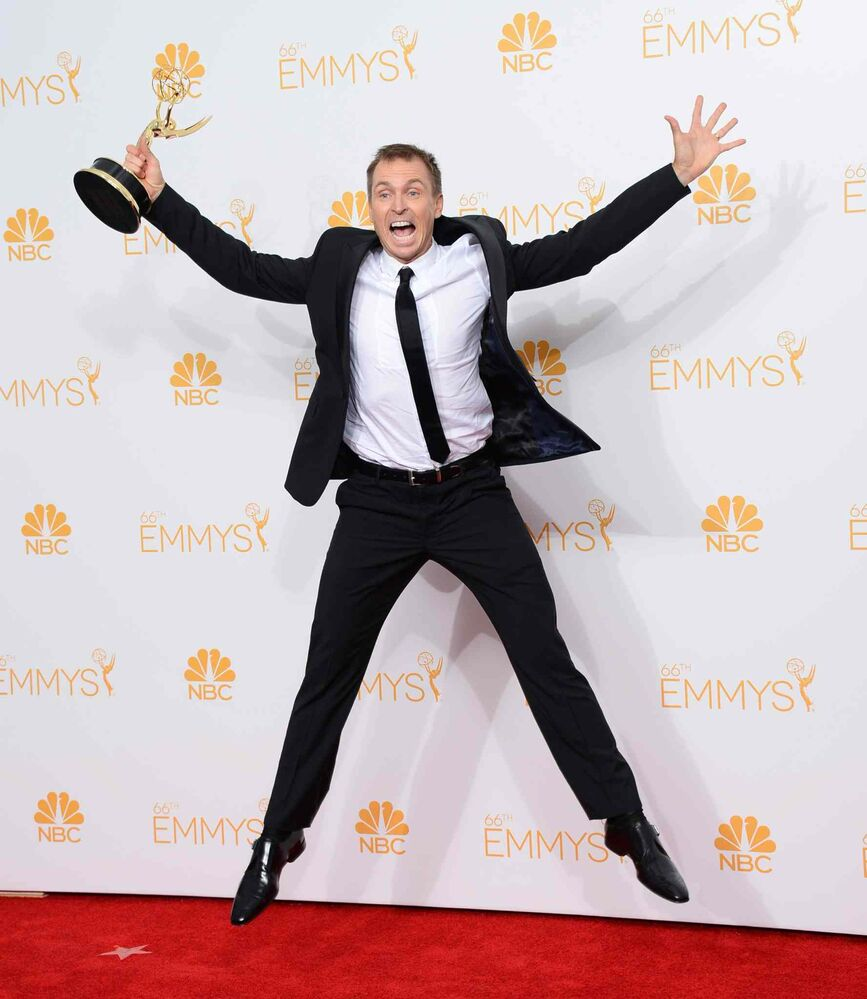 Phil Keoghan jumps for joy in the press room at the 66th Annual Primetime Emmy Awards at the Nokia Theatre L.A. Live.