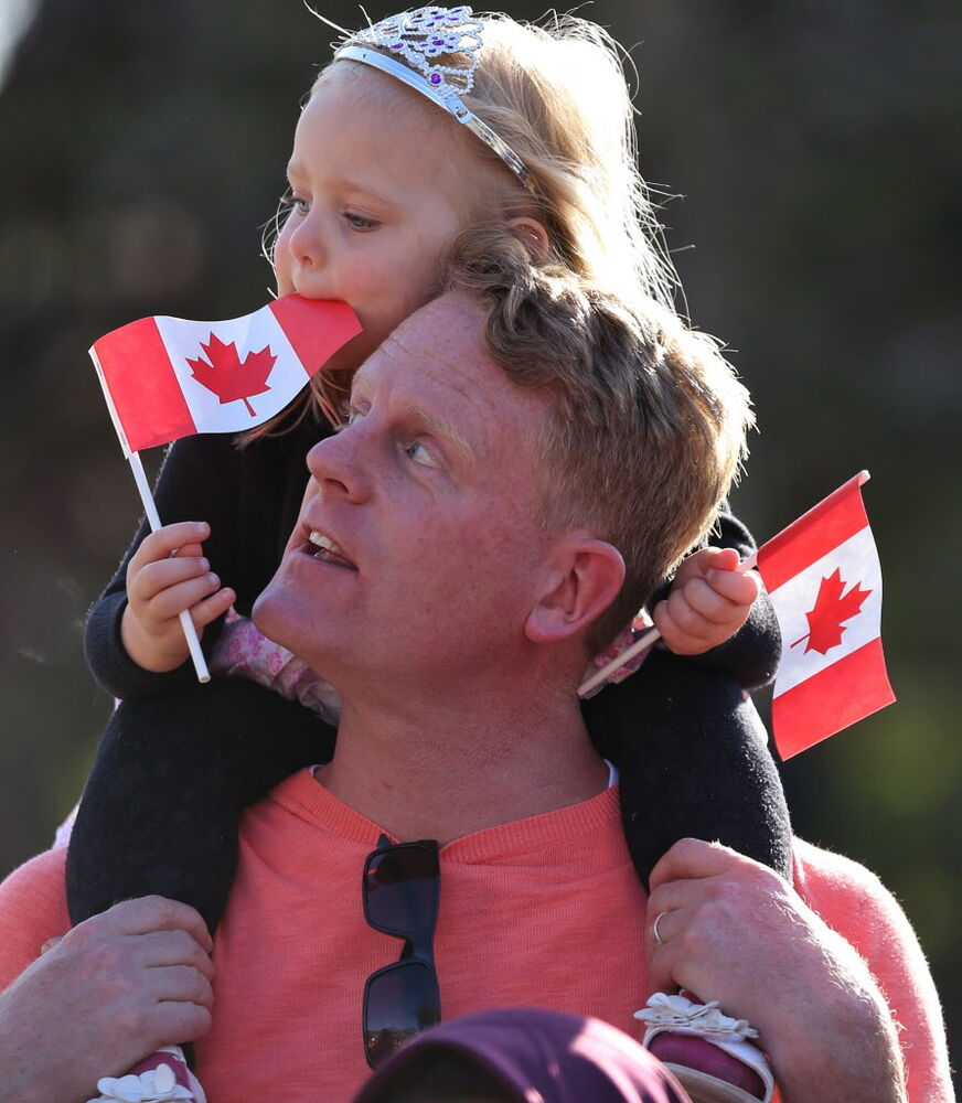 Kiri MacAulay, 3, on her dad Scott's shoulders waiting outside the legislature for Prince Charles and Camilla.  (Melissa Tait / Winnipeg Free Press )