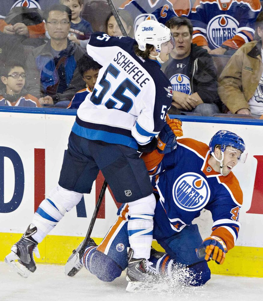 Winnipeg Jets' Mark Scheifele (55) checks Edmonton Oilers' Will Acton (41) during second-period NHL hockey action in Edmonton. (Jason Franson / The Canadian Press)