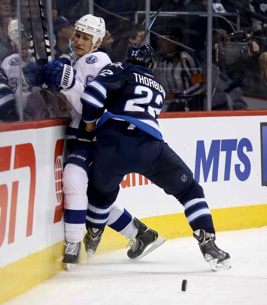 Tampa Bay Lightning's Sami Salo (6) gets slammed into the boards by Winnipeg Jets' Chris Thorburn (22) during second period. (Trevor Hagan / The Canadian Press)