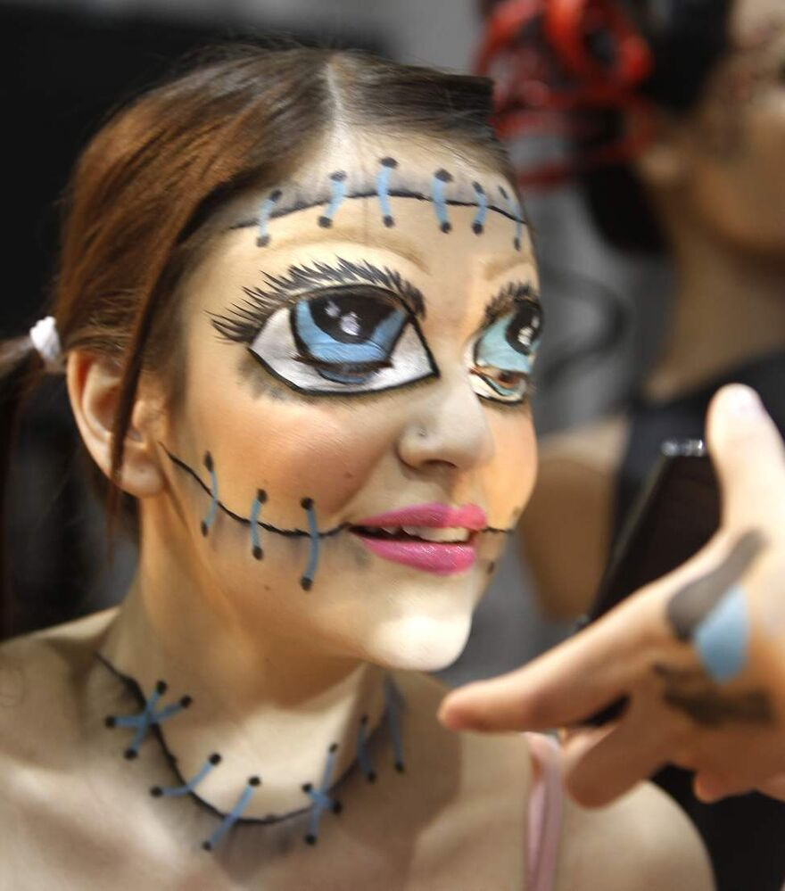 Teri Bouvier, a student in the Aesthetics program at the Arts and Technology Centre, looks at a mirror to see the fantasy makeup application on her face done by fellow student Hayley Harris on the show floor of the Rotary Career Symposium at the Winnipeg Convention Centre.  Wednesday, April 4, 2012. (WAYNE GLOWACKI / WINNIPEG FREE PRESS)