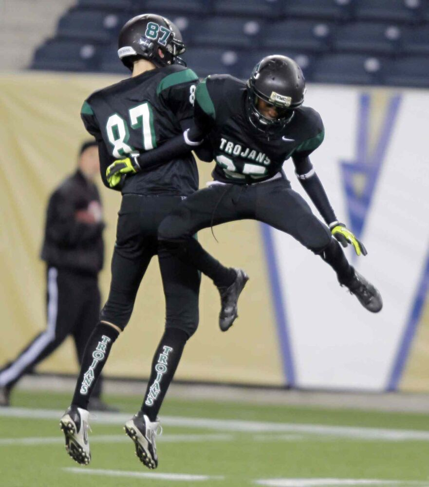 Members of the Vincent Massey Trojans celebrate on the field after their victory. (BORIS MINKEVICH / WINNIPEG FREE PRESS)
