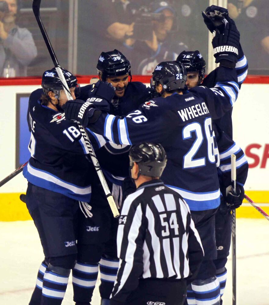 Winnipeg Jets (from left) Bryan Little, Dustin Byfuglien, Blake Wheeler and Andrew Ladd celebrate after Byfuglien's second-period goal. (BORIS MINKEVICH / WINNIPEG FREE PRESS)