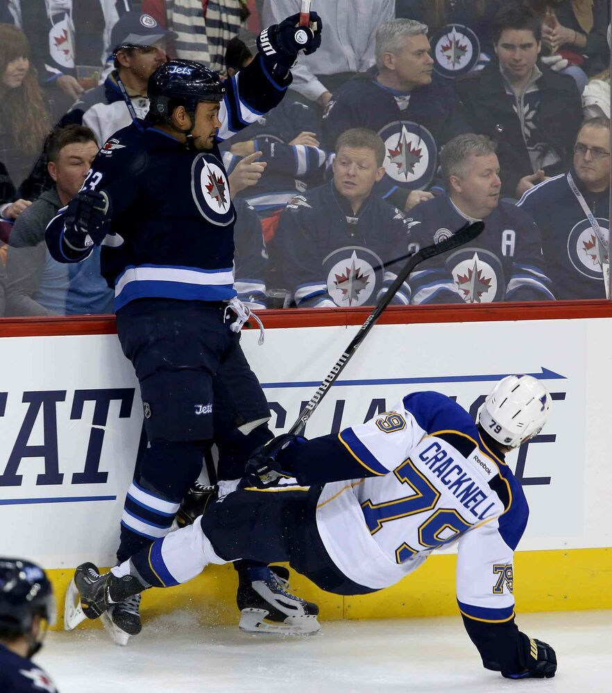 Winnipeg Jets defenceman Dustin Byfuglien lays out St. Louis Blues forward Adam Cracknell in the first period. (TREVOR HAGAN / THE CANADIAN PRESS)