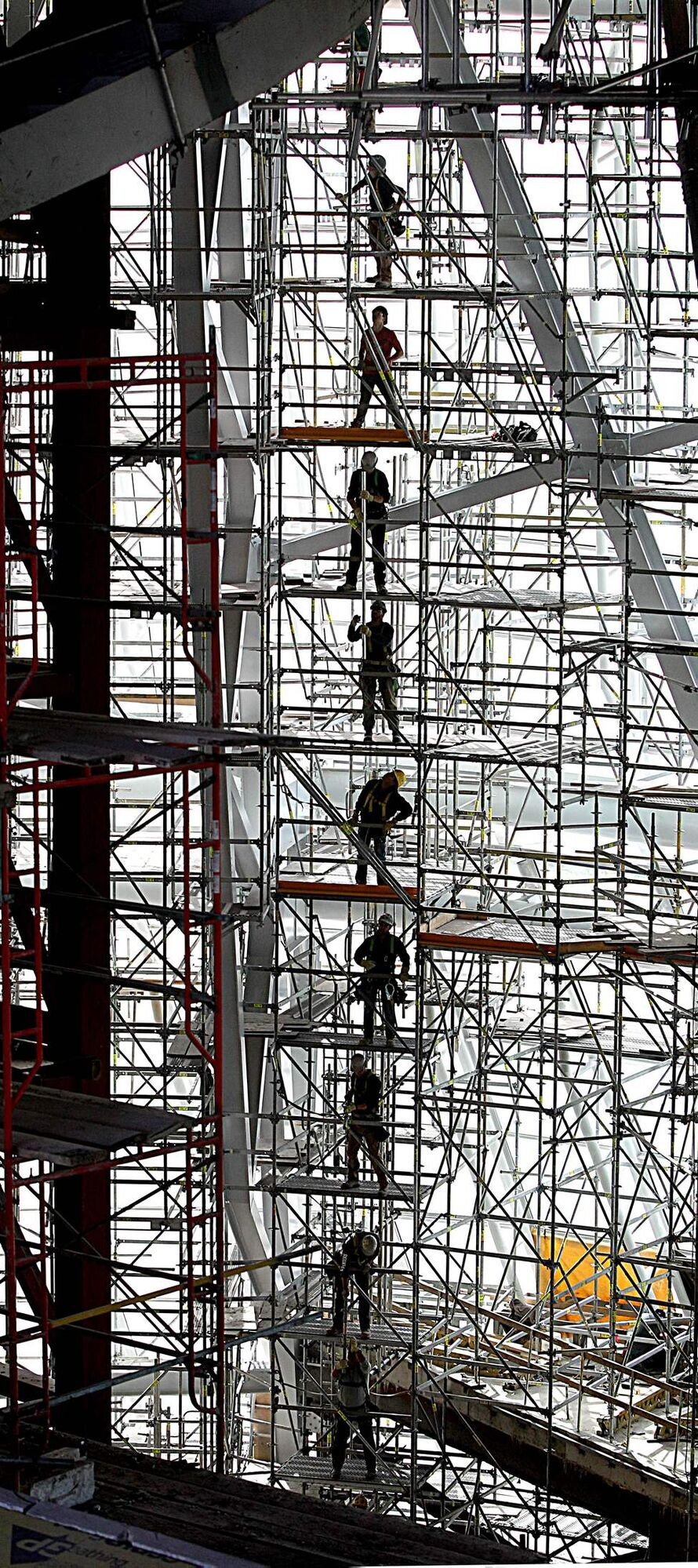 Construction crews working on the Canadian Museum for Human Rights form a human chain to remove each level of scaffolding.