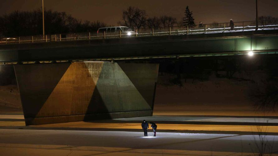 Members of the Winnipeg Police Service investigate after a man died when he fell from the St. Vital Bridge onto the frozen Red River. January 7, 2016. -