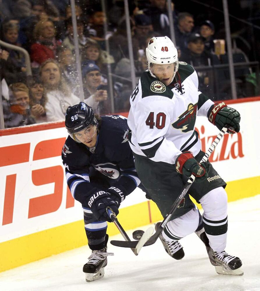 Winnipeg Jets' Mark Scheifele peers around Minnesota Wild #40 Steven Kampfer behind the Wild net in second-period action. September 19, 2013 (Phil Hossack / WInnipeg Free Press)