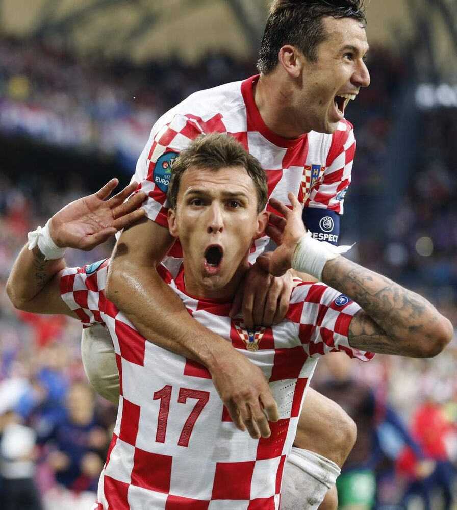 Croatia's Mario Mandzukic celebrates with his teammate Darijo Srna, top, after scoringduring the Euro 2012 soccer championship Group C match between Italy and Croatia in Poznan, Poland, Thursday, June 14, 2012. (Antonio Calanni / The Associated Press)