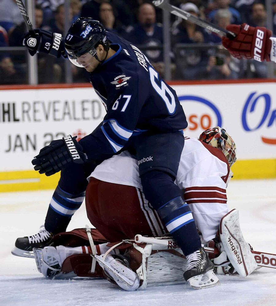 Jets forward Michael Frolik takes a seat on top of Phoenix Coyotes' goalie Mike Smith during the second period of the Jets' 5-1 victory of the Phoenix Coyotes.