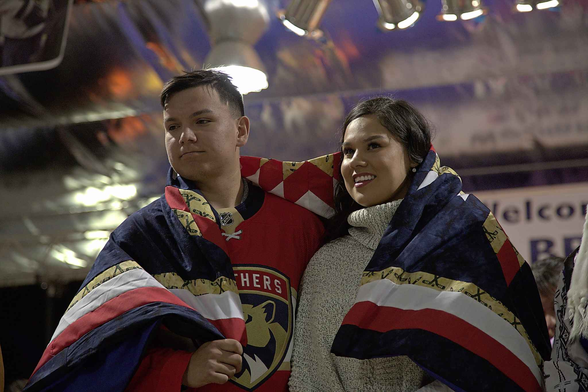 Brady Keeper and partner Shaylyn, wrapped in a blanket presented to them at a homecoming ceremony, stand for an honour song at the Cross Lake arena. MELISSA MARTIN / WINNIPEG FREE PRESS