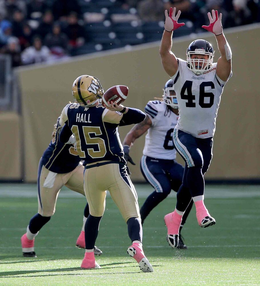 Winnipeg Blue Bombers' quarterback Max Hall (15) manages to throw a long pass over Toronto Argonauts' Jason Pottinger (46) during the second half. (TREVOR HAGAN / WINNIPEG FREE PRESS)