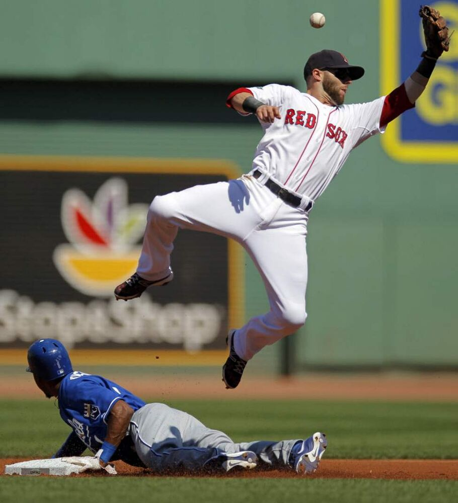 Kansas City Royals' Jarrod Dyson, bottom, steals second base as Boston Red Sox's Dustin Pedroia tries to get his glove on the ball in the first inning of a baseball game at Fenway Park. (AP Photo/Steven Senne)