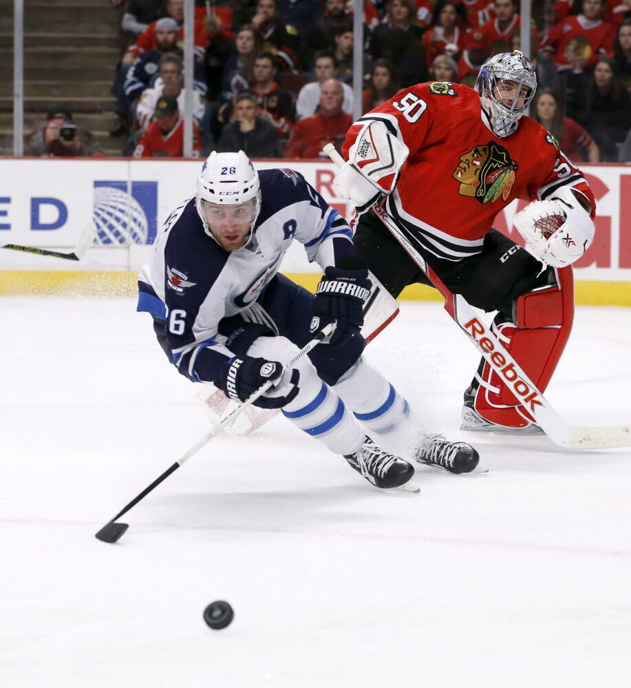 Winnipeg Jets right wing Blake Wheeler (26) chases a puck after Chicago Blackhawks goalie Corey Crawford clears it from in front of the net. (Charles Rex Arbogast / The Associated Press )