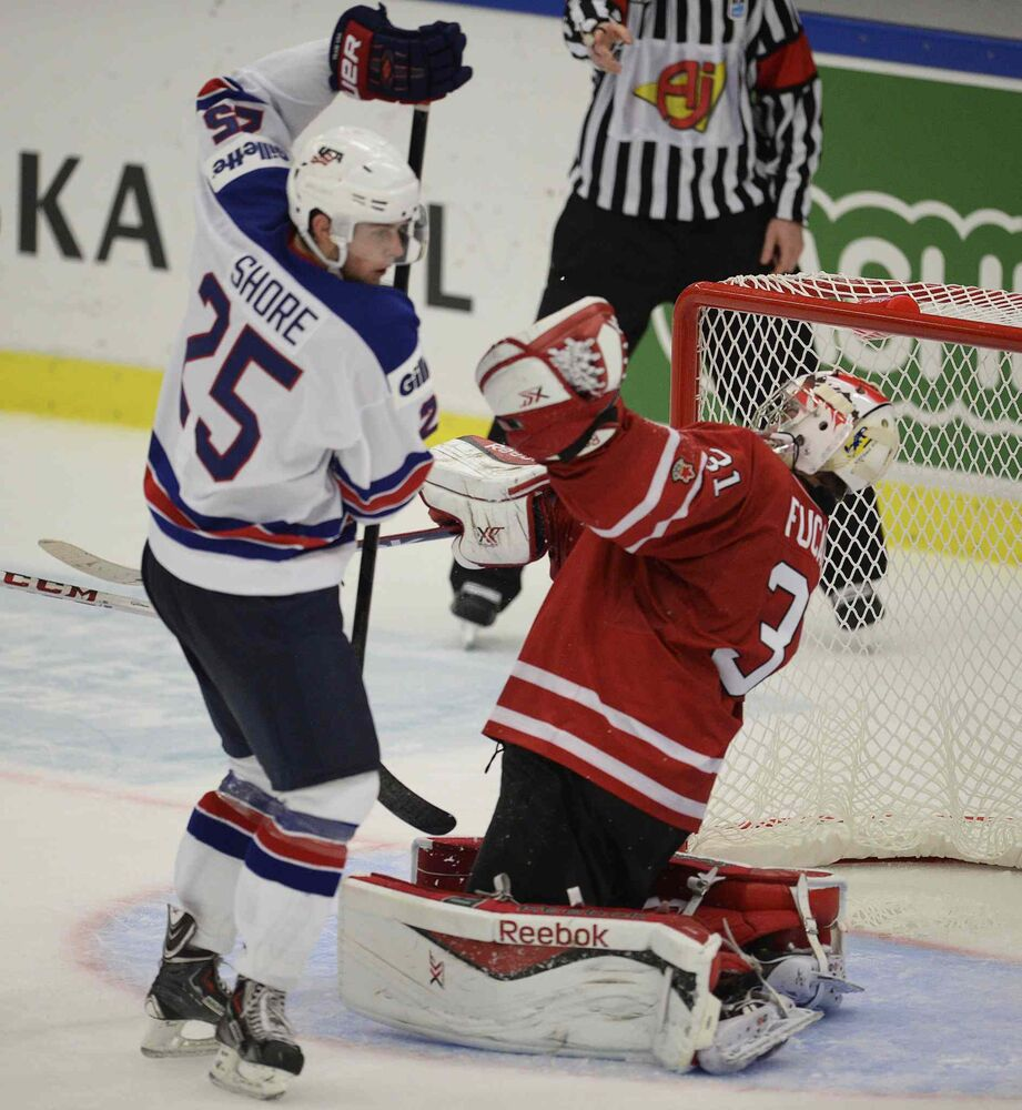 USA's Quentin Shore runs into Canada's golatender Zach Fucale during second period action. (Frank Gunn / The Canadian Press)