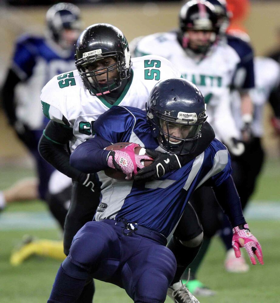 Elmwood linebacker Elvis Mingano (#55) takes down West Kildonan Wolverines running back Tyler Bryon (#21).