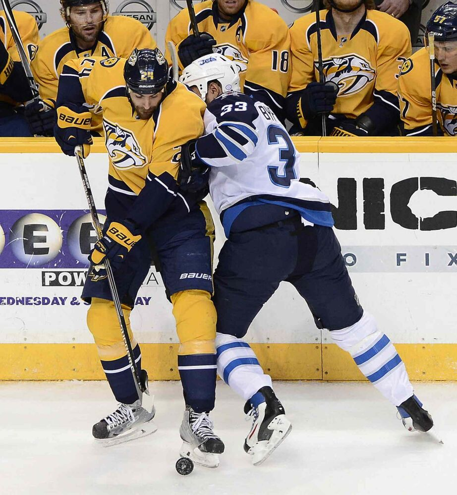 Nashville Predators left wing Eric Nystrom, left, tries to clear the puck away from Winnipeg Jets defenceman Dustin Byfuglien (33) in the first period of Thursday's game. (Mark Zaleski / The Associated Press)