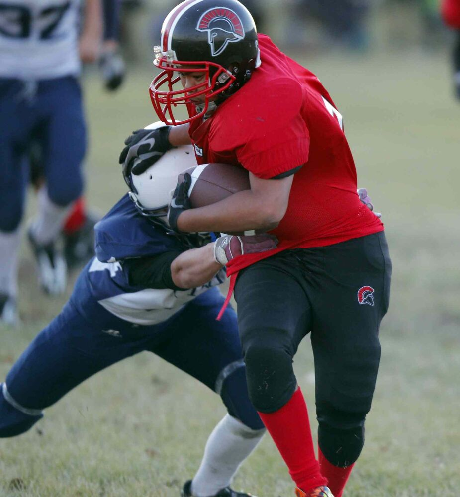 Ivan Jaque (centre) of the Sisler Spartans tries to evade the tackle of Ron Almonte of the Grant Park Pirates (left).
