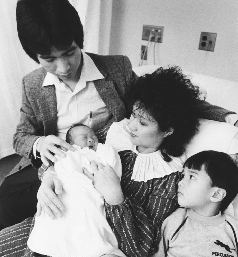 Baby Lisa Chow gets acquainted with her family after becoming the city's 1984 New Year's Baby. Born at Victoria General Hospital, the seven-pound, 6.5 ounce infant was born three minutes and 25 seconds after midnight nine days early. Chow is the daughter of Patrick and Wing-Mui, and is sister to Alan (right). (Wayne Glowacki / Winnipeg Free Press)