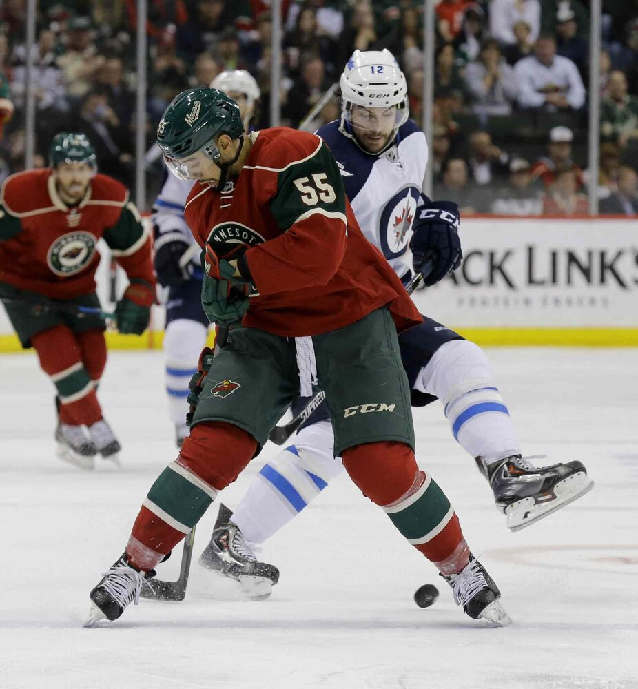 Minnesota Wild defenseman Matt Dumba (55) and Winnipeg Jets right wing Drew Stafford (12) battle for the puck during the second period of Monday's game. The Jets won the game 2-0. (Ann Heisenfelt / The Associated Press)