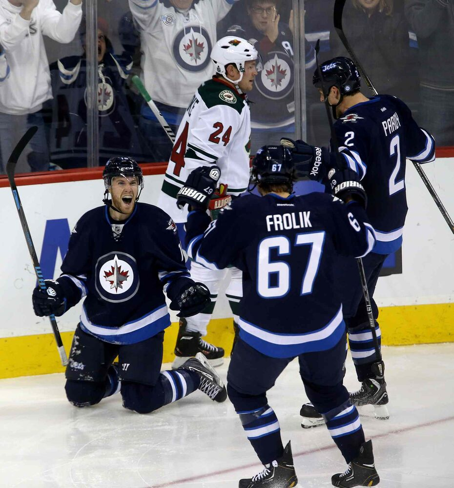 Matt Halischuk (left) celebrates with Michael Frolik (67) and Adam Pardy (2) after scoring during the third period as Matt Cooke of the Minnesota Wild looks on. (TREVOR HAGAN / WINNIPEG FREE PRESS)
