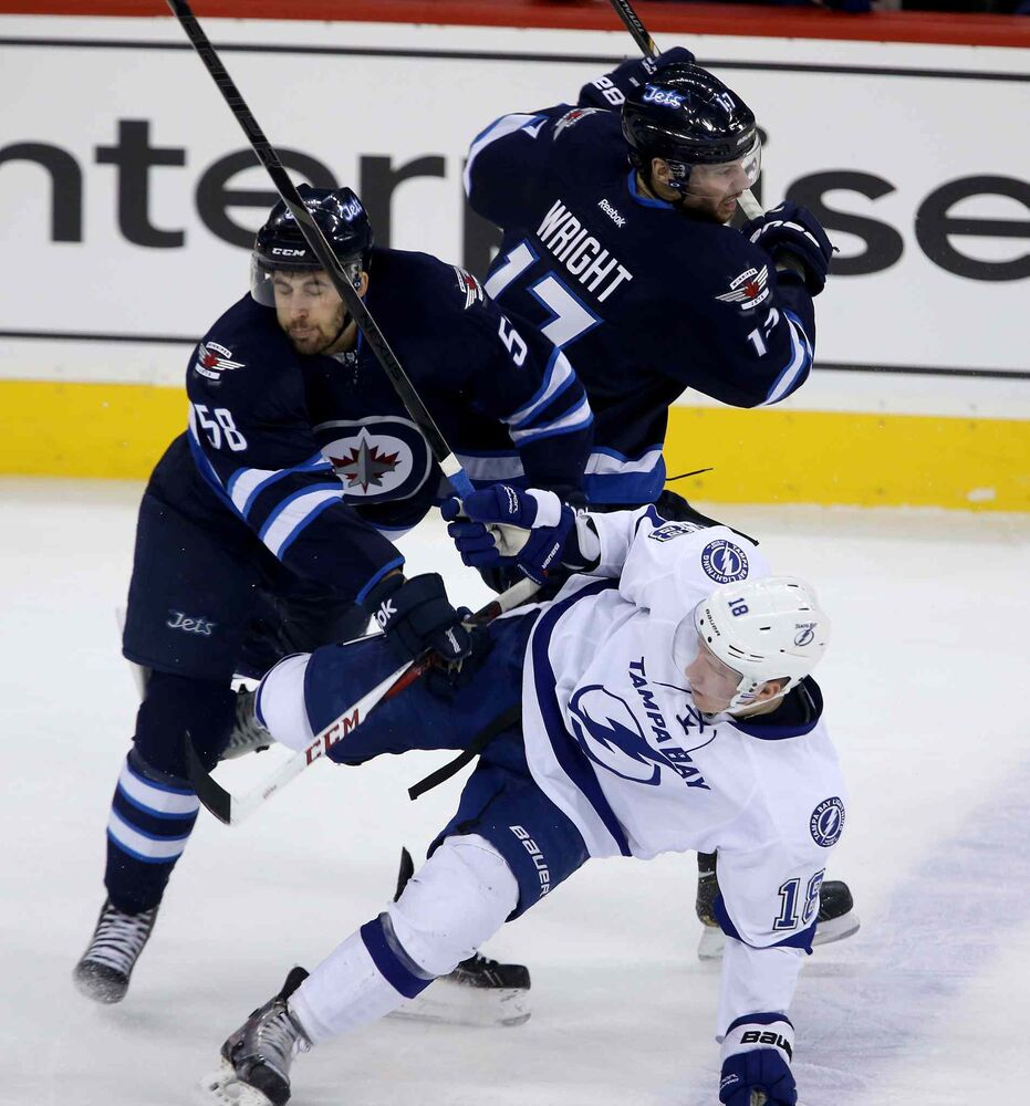 Winnipeg Jets' Eric O'Dell (58) and James Wright (17) collide with Tampa Bay Lightning's Ondrej Palat (18) during first period.