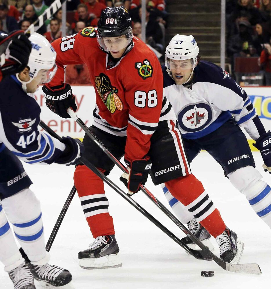 Chicago Blackhawks' Patrick Kane (88) controls the puck against Winnipeg Jets' Devin Setoguchi, left, and Eric Tangradi during the second period. (Nam Y. Huh / The Associated Press)