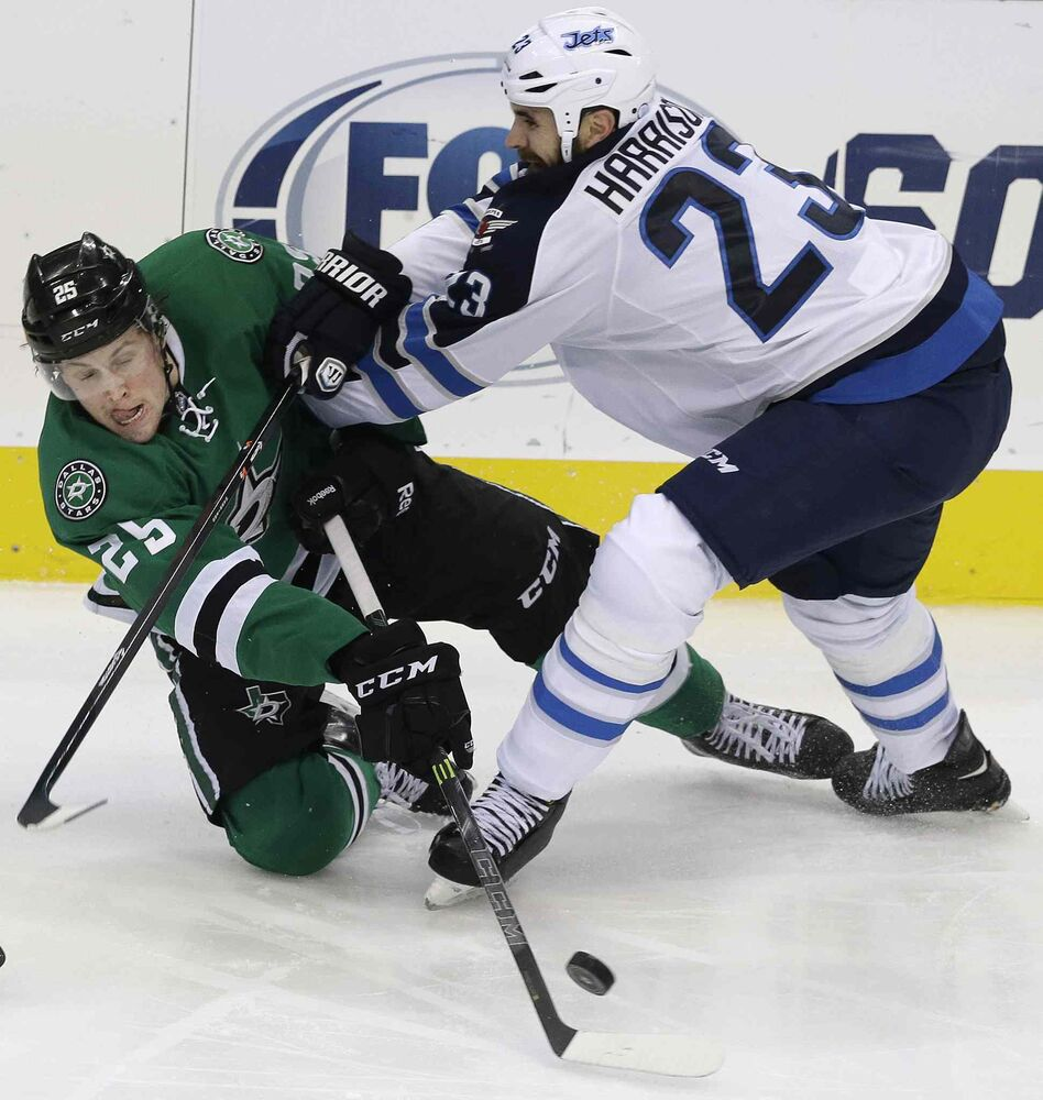 Winnipeg Jets defenceman Jay Harrison (23) and Dallas Stars right wing Brett Ritchie (25) battle for control of the puck during the second period of Thursday's game. (LM Otero / The Associated Press)