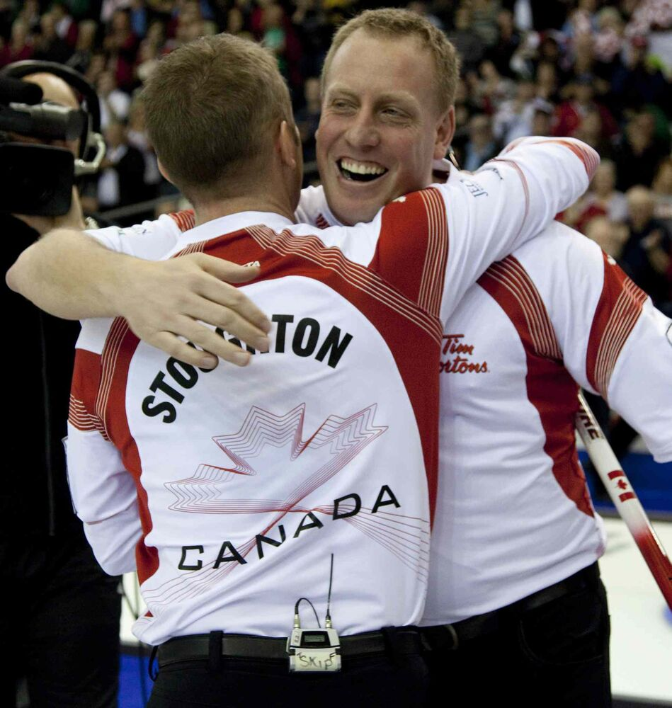 Jeff Stoughton celebrates his team's gold medal win over Scotland with lead Steve Gould at the 2011 Ford World Men's Curling Championships in Regina.    (Jonathan Hayward / The Canadian Press Files)