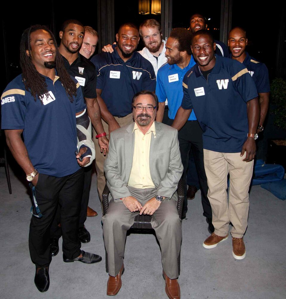 Winnipeg Blue Bombers past and present came out to support Variety, the Children's Charity of Manitoba, at Earls St. Vital on Aug. 25, 2015. The Hearts of Blue and Gold fundraising dinners are held twice a year. Here, Variety CEO Jerry Maslowsky is flanked by Bombers.  (JOHN JOHNSTON / WINNIPEG FREE PRESS)