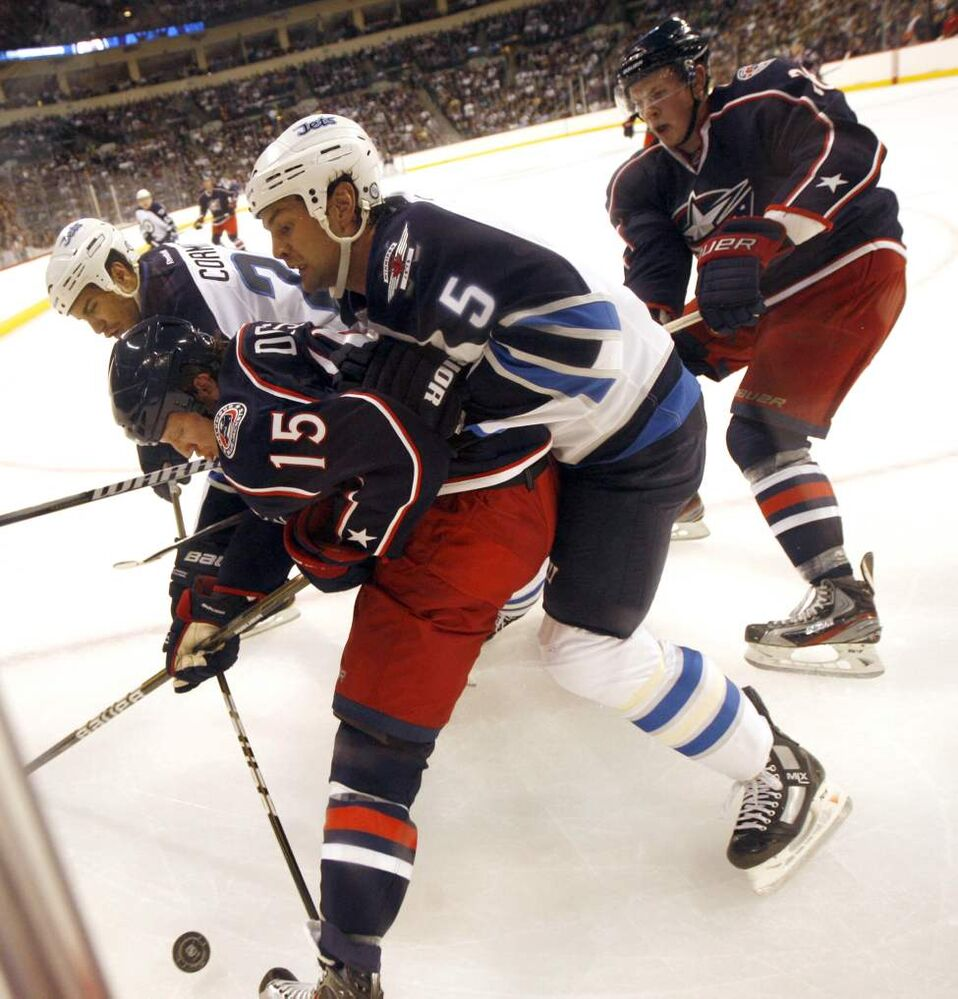 Jets #5 Mark Stuart fights for possession in the corner against Columbus' #15 Derek Dorsett in the Jets' first home game in 15 years. (Phil Hossack / Winnipeg Free Press)