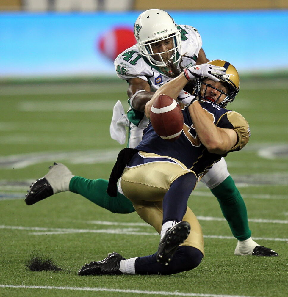 Winnipeg Blue Bombers Julian Feoli-Gudino (83) gets all wrapped up in Saskatchewan's Tyron Brackenridge's (41) defence late in the game against the Saskatchewan Roughriders Thursday.  (Phil Hossack / Winnipeg Free Press)