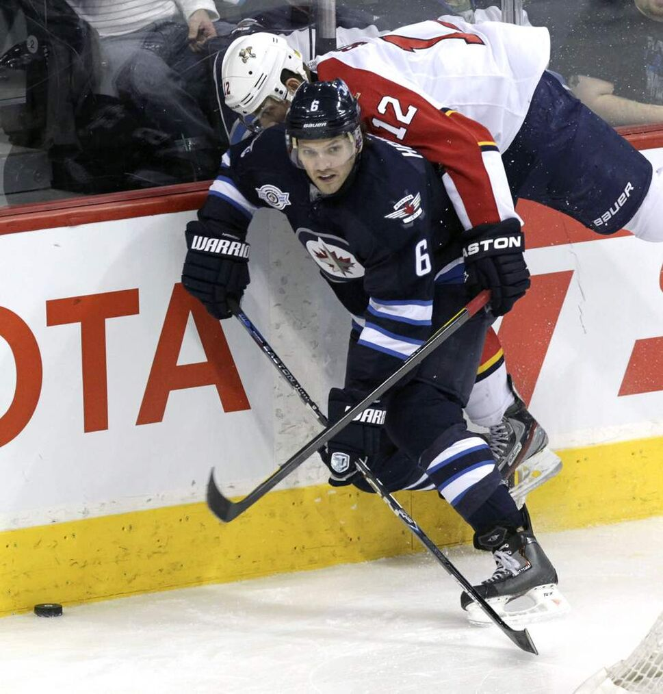 Winnipeg Jets' Ron Hainsey (6) controls the puck behind the Jets net while Florida Panthers' Jack Skille (12) falls on him in the third period. January 21, 2012 (MIKE DEAL / WINNIPEG FREE PRESS)