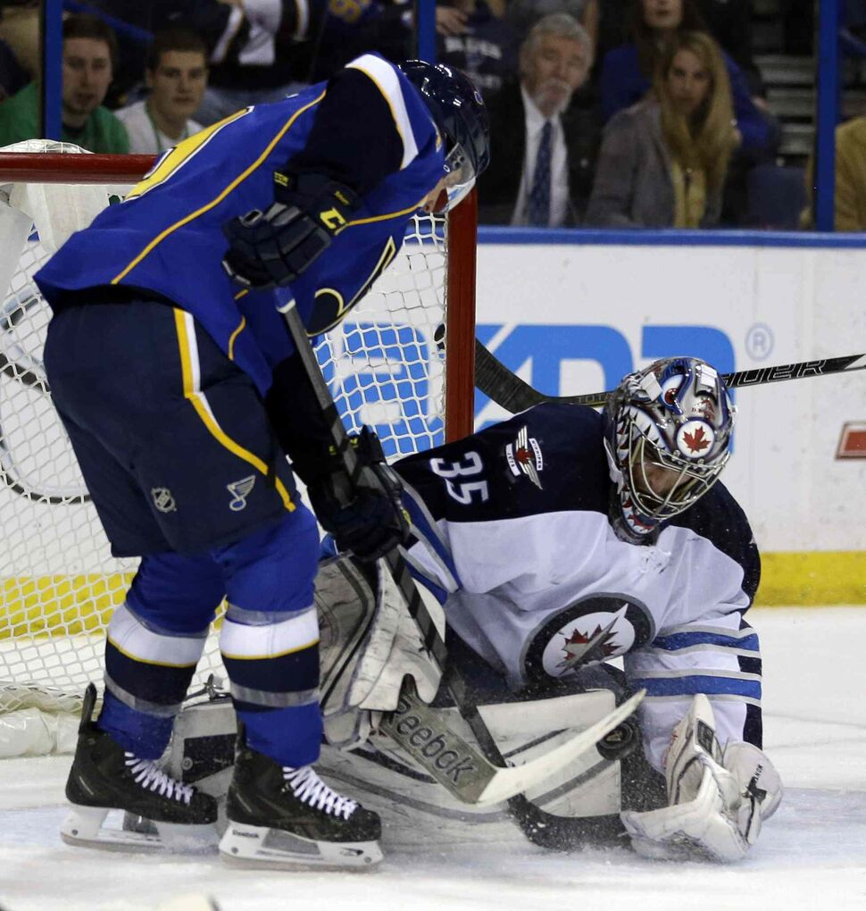 Blues forward Jaden Schwartz tries to get his stick on a loose puck as Jets goalie Al Montoya defends during the second period. (JEFF ROBERSON / THE ASSOCIATED PRESS)