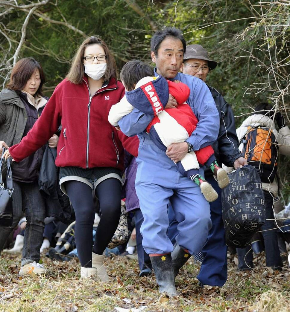 People evacuate to higher place after tsunami warning was issued in Higashimatsuyshima, Miyagi Prefecture, northern Japan, Monday, March 14, 2011, three days after northeastern coastal towns were devastated by an earthquake and tsunami. (AP Photo/Kyodo News)