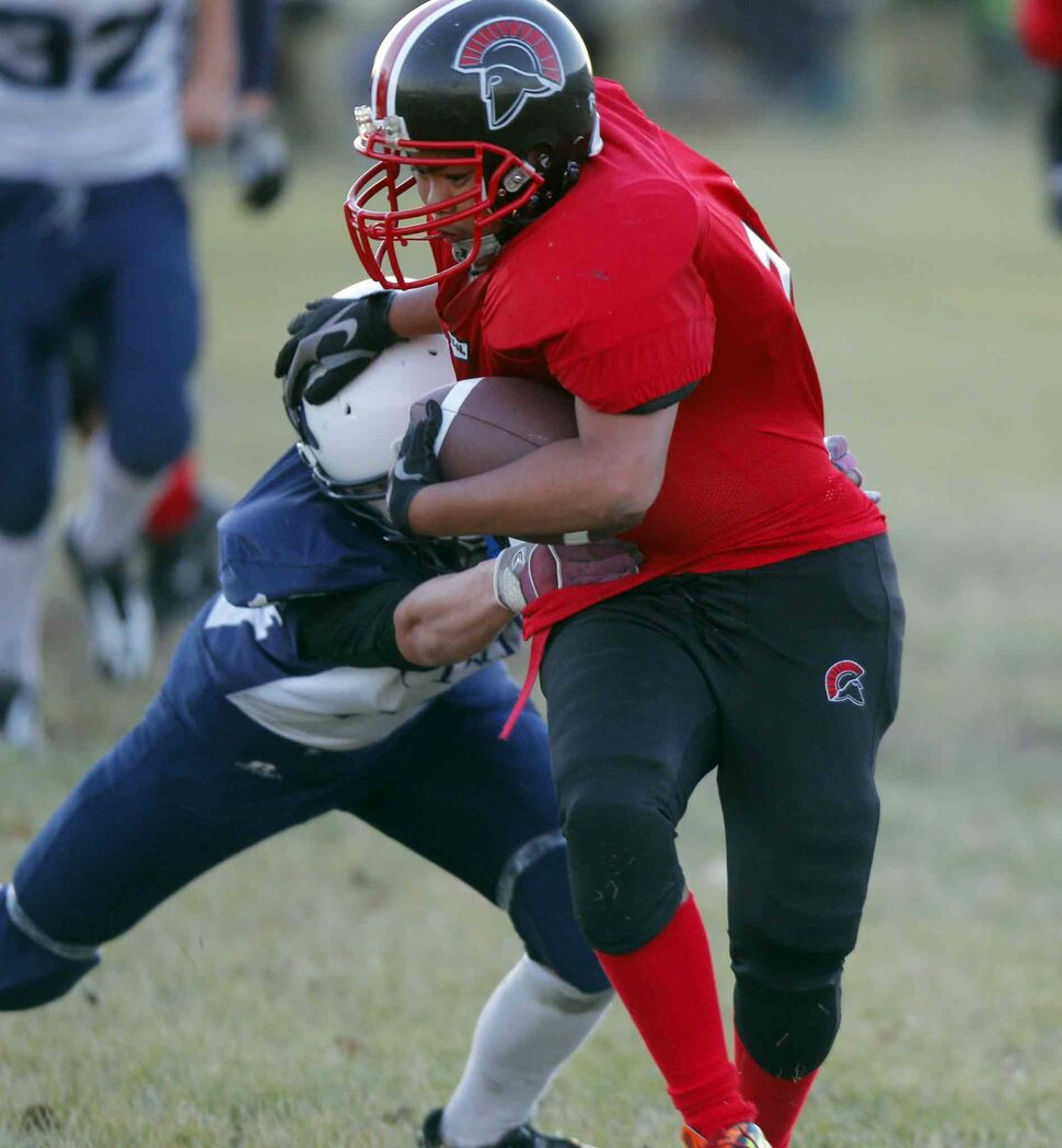 Ivan Jaque (centre) of the Sisler Spartans tries to evade the tackle of Ron Almonte of the Grant Park Pirates (left). (BORIS MINKEVICH / WINNIPEG FREE PRESS)