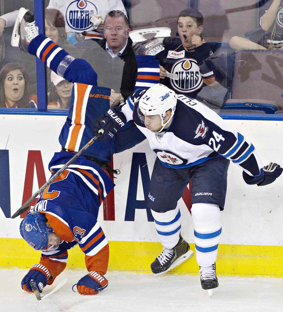 Winnipeg Jets defenceman Grant Clitsome (24) checks Edmonton Oilers forward Linus Omark (23) during the third period. (Jason Franson / The Canadian Press)