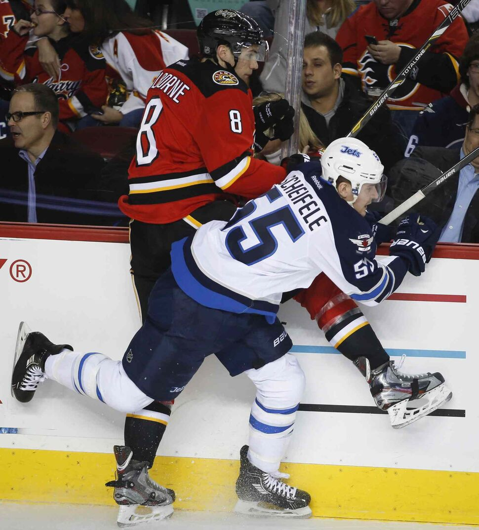 Winnipeg Jets' Mark Scheifele, right, checks Calgary Flames' Joe Colborne during the second period in Calgary Thursday. (Jeff McIntosh / The Canadian Press)