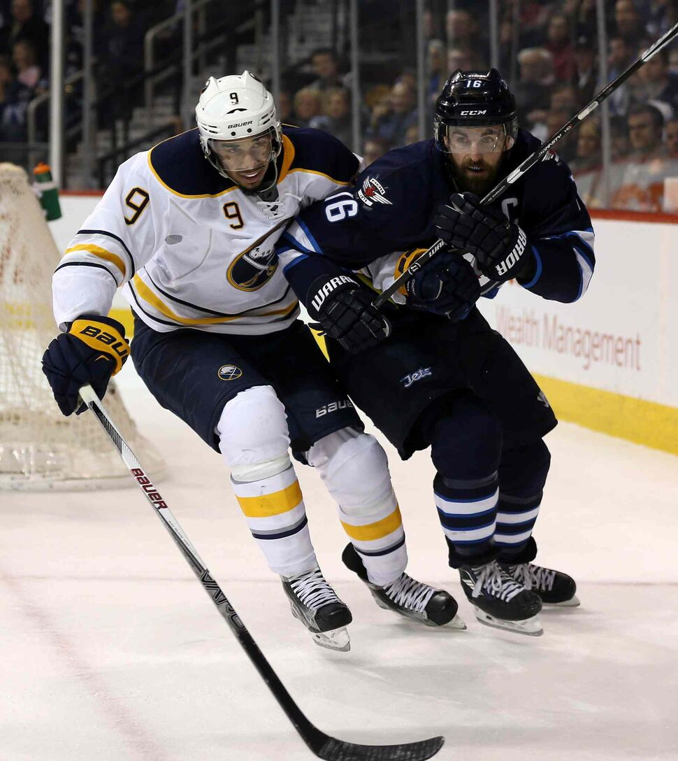 Buffalo Sabres' Evander Kane (9) collides with Winnipeg Jets' Andrew Ladd (16) while fighting for the puck during the second period. (Trevor Hagan / The Canadian Press)