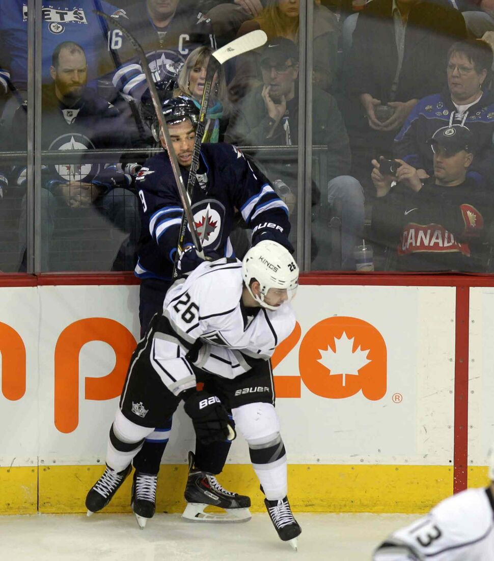 Evander Kane is framed in sticks as he's put into the boards by L.A. Kings' Slava Noyov at the MTS Center Thursday. (Phil Hossack / Winnipeg Free Press)
