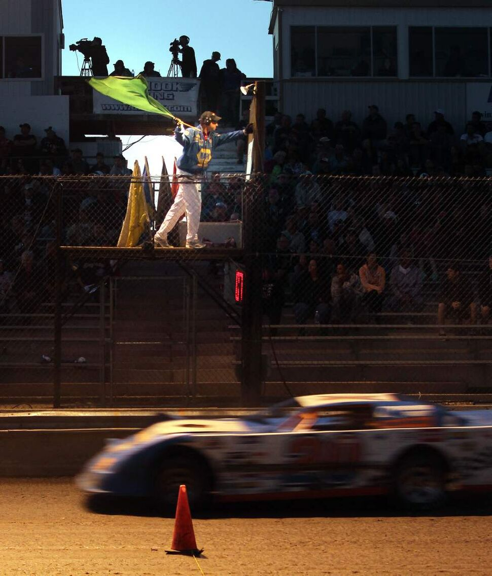 Rob Comeau gives the racers a green flag to start the action.