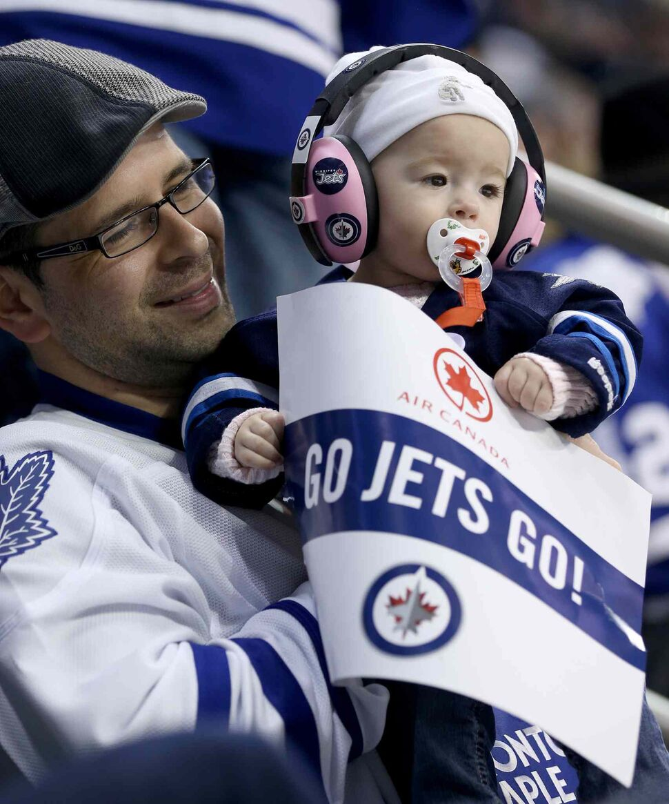 Adam Hagarty and nine-month-old Mayla Hagarty watch the Winnipeg Jets play the Toronto Maple Leafs at MTS Centre Saturday.  (Trevor Hagan / Winnipeg Free Press)