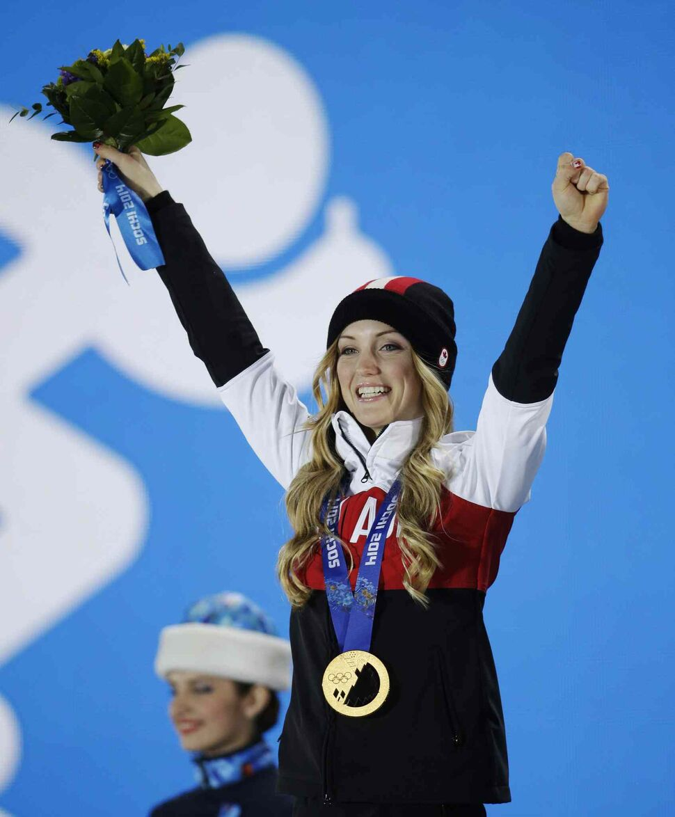 Women's moguls gold medalist Justine Dufour-Lapointe of Canada celebrates during the medals ceremony at the 2014 Winter Olympics. (Morry Gash / The Canadian Press)