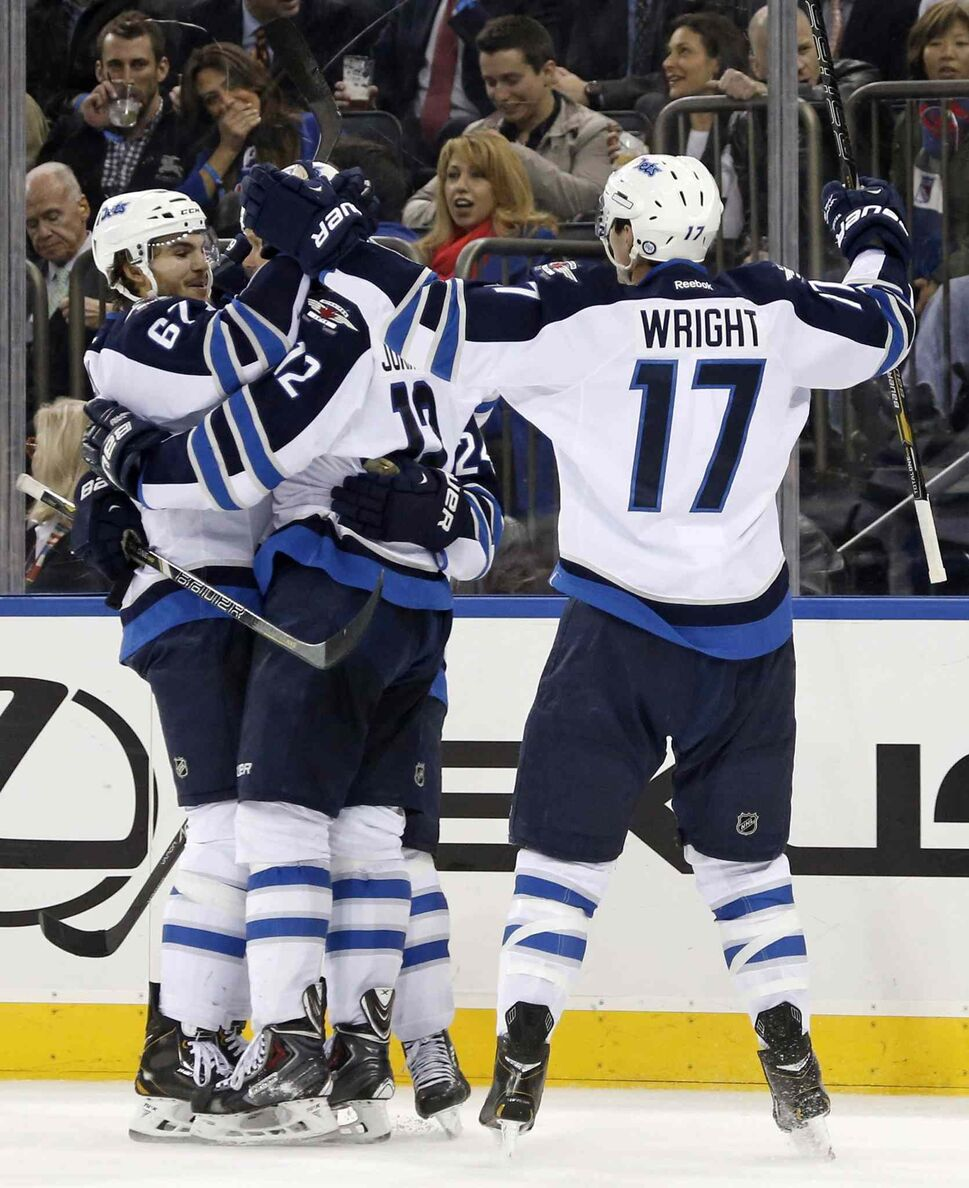 Winnipeg Jets players Michael Frolik (from left), Olli Jokinen and James Wright celebrate a third-period goal by Jokinen. (KATHY WILLENS / THE ASSOCIATED PRESS)