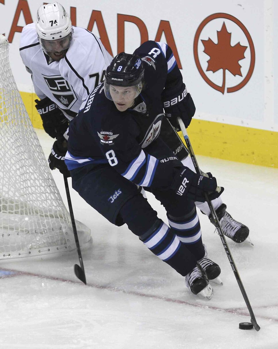 Jacob Trouba (8) takes control of the puck from behind the Jets' net while Los Angeles Kings' Dwight King (74) is hot on his heels in the second period. (MIKE DEAL / WINNIPEG FREE PRESS)