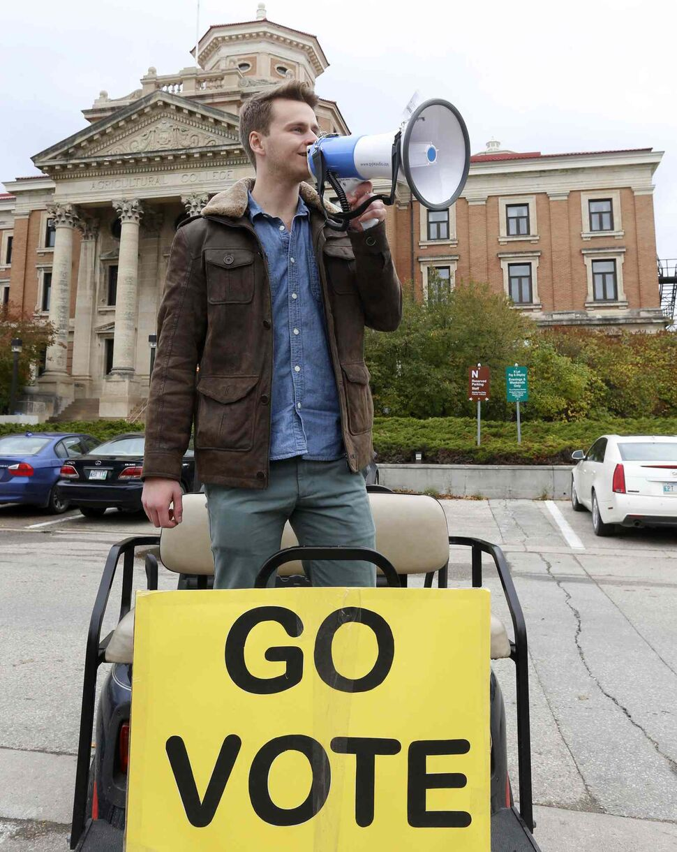 Jeremiah Kopp, president of the University of Manitoba Student Union using a megaphone driving around with a cart is encouraging students to vote at the polling station at Pembina Hall Student Lounge on the campus. ( Wayne Glowacki / Winnipeg Free Press)