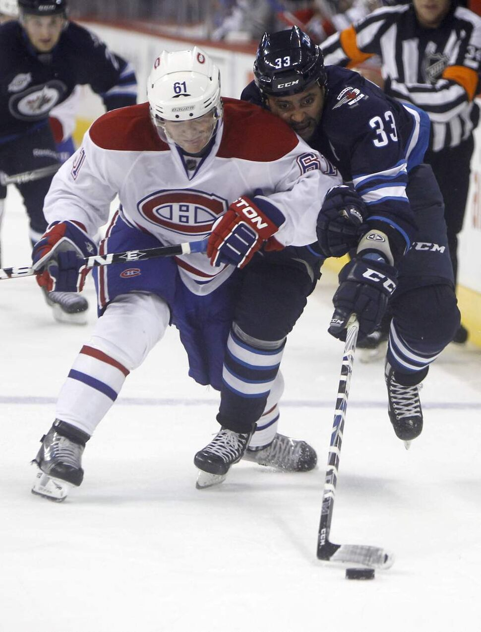Winnipeg Jets' Dustin Byfuglien battles for the puck with Canadien Raphael Diaz during second-period action in the NHL regular season home opener Sunday, October 9, 2011 at the MTS Centre. (Trevor Hagan / Winnipeg Free Press)